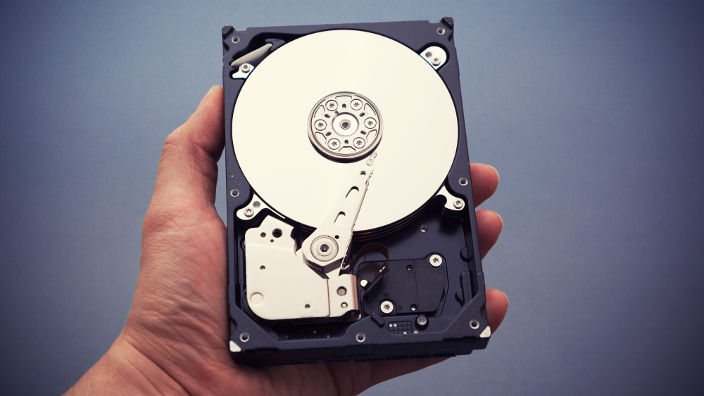 Hand holding an internal hard drive open faced